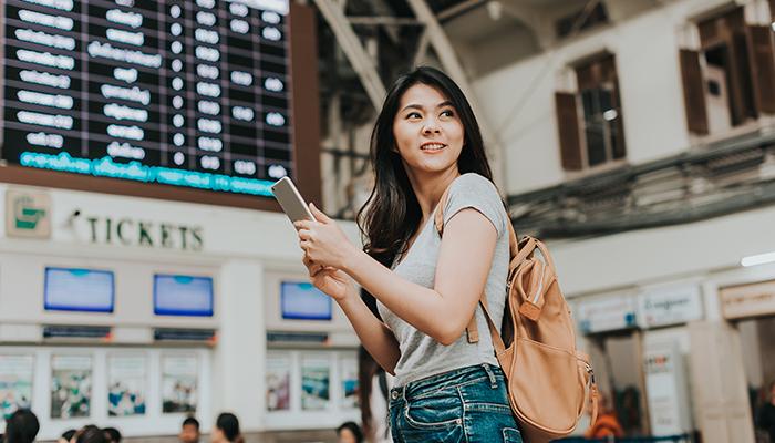 スマートフォンを片手に旅をする女性
